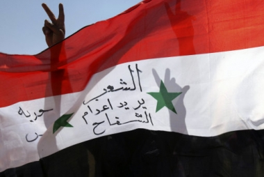 syrian-expatriates-gesture-as-they-hold-a-syrian-national-flag-during